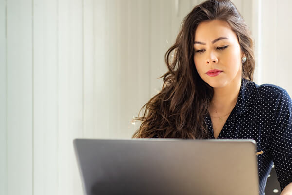 woman working on laptop computer filling out a COVID microloan application