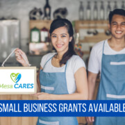 man and woman in retail shop holding a mesa cares sign with text: Small Business Grant