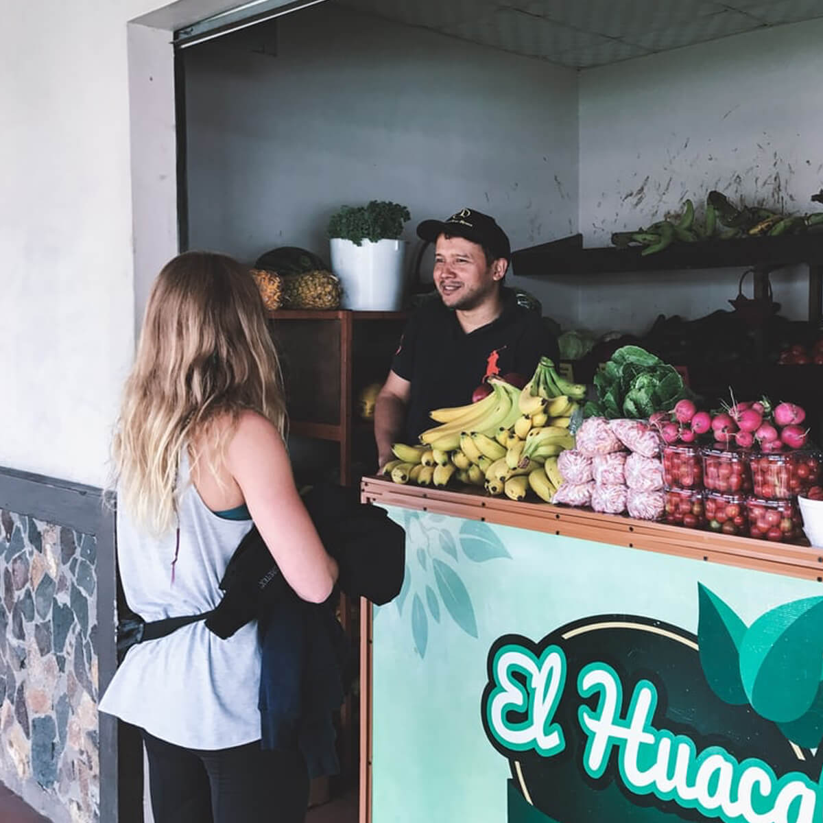 Fruit smoothie business owner standing next to fruit on counter with client at his juice stand