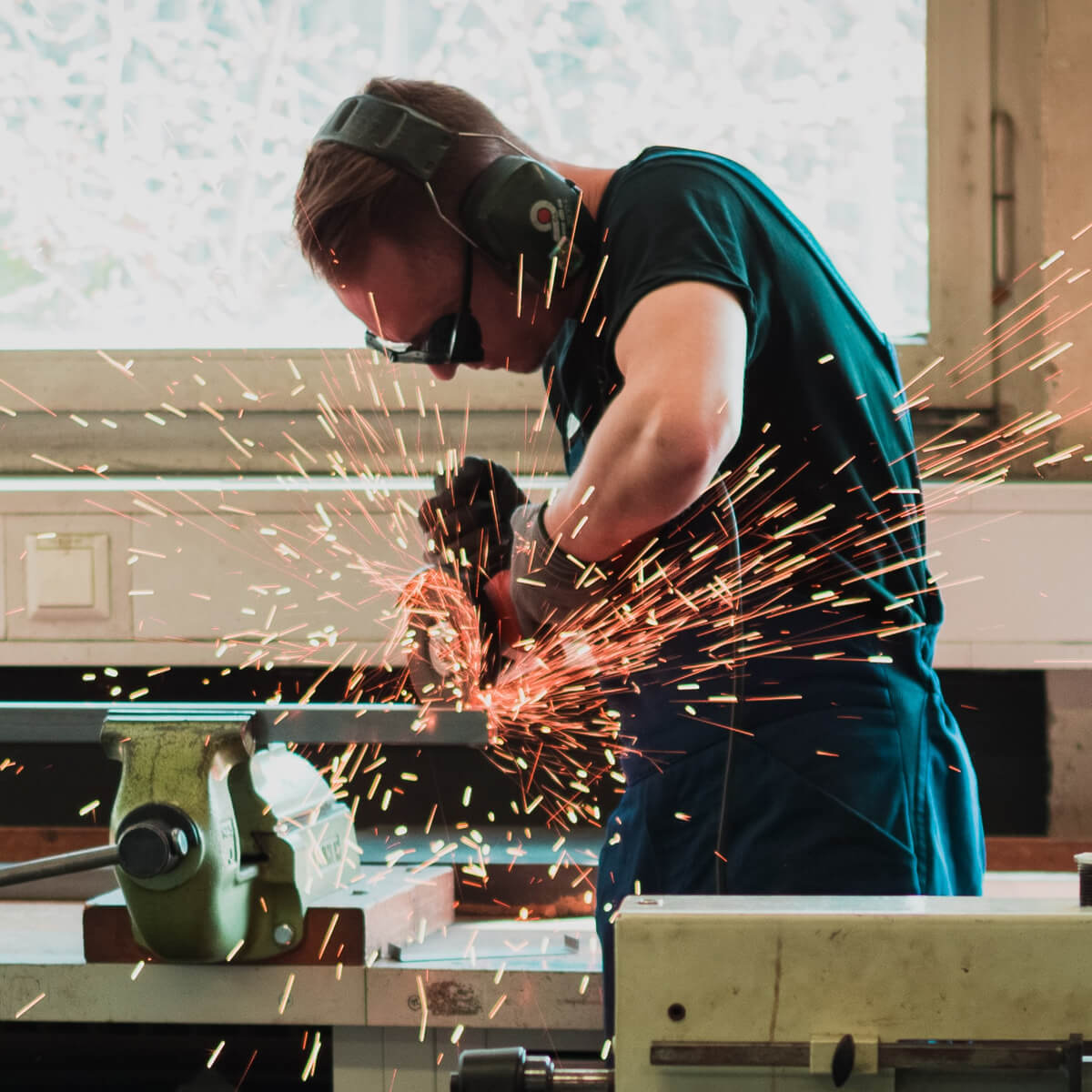 Man using saw with sparks flying out
